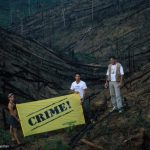 """Paulo Adario and two other activists holding a banner """"CRIME"""" in the Amazon forest, Para State, Brazil."""